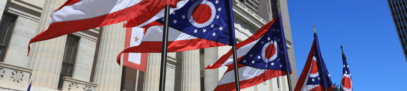 Several Ohio state flags being flown in front of the Statehouse in Columbus, Ohio.
